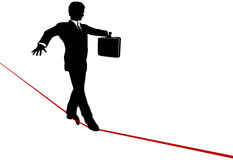 Business Man Balance Act on Risk Tightrope. A business man walks a high wire tightrope, above risk and danger, the businessman balances with a briefcase Royalty Free Stock Photo