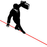 Business Man Balance Risk Tightrope from Above. A business man walks a high wire tightrope, above risk and danger, the businessman balances with a briefcase Royalty Free Stock Image