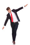Business man balancing. Full length picture of a young business man balancing on an imaginary rope and looking down. isolated on white background Stock Photography