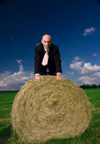 Business man on a bale of hay Stock Images