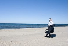 Business Man on Beach. Adult man in business suit stands on a sandy beach near the shoreline next to a black leather executive chair.  Model has slung his jacket Royalty Free Stock Photography