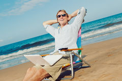 Business Man on the Beach. Business man relaxing at the beach with lap top computer Royalty Free Stock Photo