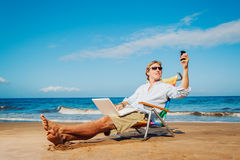 Business man on the beach. Young Business Man Working Remotely on Tropical Beach Royalty Free Stock Photos