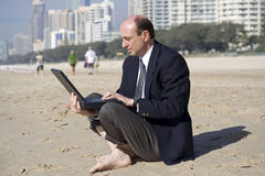 Business man on the beach. Image attempting to portray mobility in todays business world Royalty Free Stock Photo