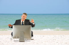 Business man on the beach with a computer Stock Photos