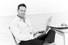 Business man on beach with laptop. Business man sitting on a chair on the beach with laptop stock photos