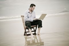 Business man on the beach with laptop Royalty Free Stock Photo