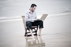 Business man on the beach with laptop. Business man sitting on a chair on the beach with laptop stock image