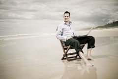 Business man on the beach with laptop. Business man sitting on a chair on the beach with laptop stock photography