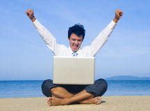 Business man on beach with laptop.  stock photo