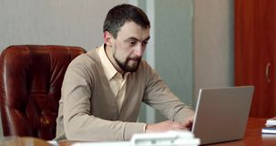 Business man with a beard having a video chat in his office. stock video footage