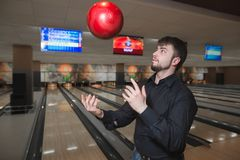 A business man with a beard juggles a bowling ball against a background of playing tracks. Playing bowling club. A business man with a beard juggles a bowling Royalty Free Stock Image