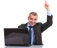 Business man behind laptop points up Stock Images