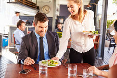 Business man being served food in a restaurant Stock Photography