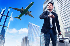 Business man and big belonging luggage watching to sky and hand. Watch time against high building skyscrapers and passenger jet plane flying above use for royalty free stock photos