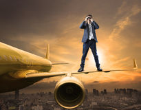 Business man and binoculars lens standing on plane wing spying. Acting use for commercial competition and top secret strategy Royalty Free Stock Image