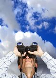 Business man with binoculars over sky Stock Image