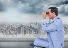 Business man with bionoculars against grey skyline and clouds. Digital composite of Business man with bionoculars against grey skyline and clouds Stock Photo