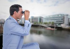 Business man with bionoculars against water across from blurry buildings. Digital composite of Business man with bionoculars against water across from blurry Stock Photo