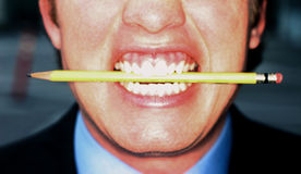 Business man biting pencil. Business man is biting down on yellow pencil stock images