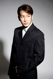Business man in black coat. Handsome asian business man in formal attire Royalty Free Stock Images