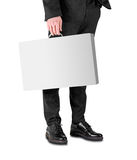 Business man in a black suit and shoes holds a white box with a handle Stock Images