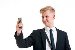 Business man in black suit taking a self-portrait with his phone Royalty Free Stock Images