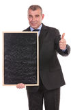 Business man with blackboard shows thumb up Stock Photo