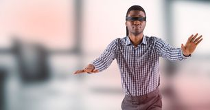 Business man blindfolded against blurry grey office with red overlay Stock Image