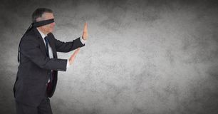 Business man blindfolded with grunge overlay against grey background Stock Images