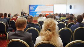 Business man and blonde woman with long hair and people listening on the conference or on the training in the hall.  royalty free stock photos