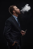 Business man blowing smoke of electronic cigarette Stock Images