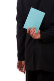 Business man with a blue letter behind his back Stock Images