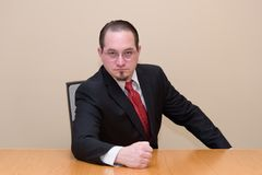 Business man in a boardroom. Male model in a nice suit, seated in a boardroom listens to your big pitch Royalty Free Stock Photo
