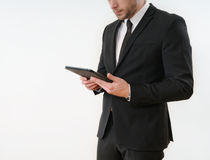 Business man body side in black suit holding his tablet on white Royalty Free Stock Photos