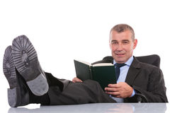 Business man with book and with feet on desk looks at you Royalty Free Stock Image