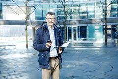 Business man. A man with a book and a laptop. The guy speaks through the phone on the street. The guy in the glasses. Business man. A man with a book and a Royalty Free Stock Photos