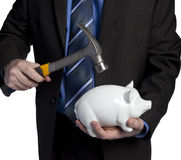 Business man breaking piggy bank with hammer Royalty Free Stock Photography