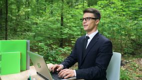 Business man breathing fresh air in eco-friendly office, sitting at desk in park stock video