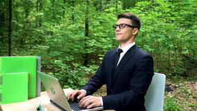Business man breathing fresh air in eco-friendly office, sitting at desk in park stock image