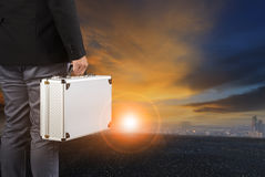 Business man and breifcase standing against sun rising sky with Stock Photos
