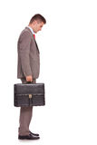 Business man with briefcase looking down Royalty Free Stock Photography