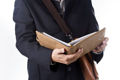 Business man with briefcase and reading the book Stock Photography