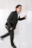 Business man with briefcase running stock image