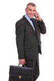 Business man with briefcase speaks on the phone Stock Photo