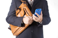 Business man with briefcase and using smart phone Royalty Free Stock Image