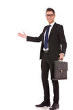 Business man with a briefcase welcoming. Smiling business man with a briefcase welcoming you on white background Stock Photography