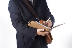 Business man with briefcase and writing the book Stock Photography
