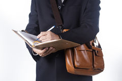 Business man with briefcase and writing the book Stock Images