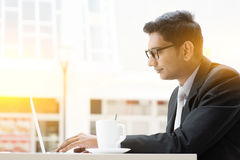 Business man browsing internet at cafe. Side view of Indian businessman at cafeteria, having a cup of coffee and using internet royalty free stock photography
